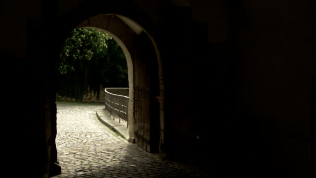 A woman runs through an archway over a cobblestone street. Available in HD