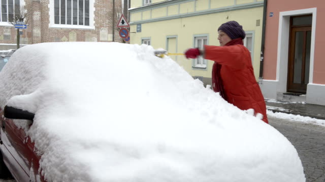 A woman scrapes snow and ice from a car window