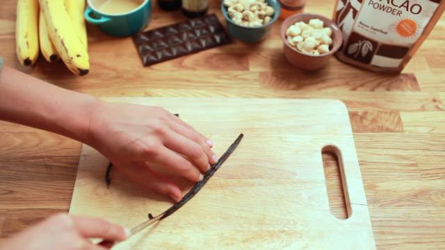 POV woman scraping a vanilla bean