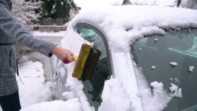 Woman scraping snow off the car