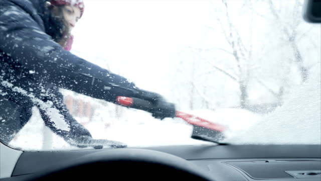 Woman scraping snow off the car windshield.
