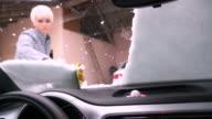 Vrouw sneeuw uit de auto voorruit schrapen