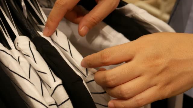 Woman select shirt at shopping mall , 4k resolution (UHD3840)