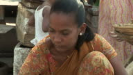 WS woman selling ginger at street market / Dharavi, Mumbai, India