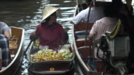 A woman sells fruit from her small boat to passing customers. Bangkok, Thailand.