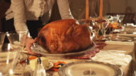 CU Woman serving turkey at decorated Thanksgiving table, mid section / Lehi, Utah, USA