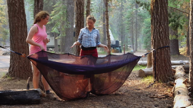 Woman Setting Up Camping Hammock With Friend Watching