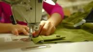 CU of woman sewing zipper on coat