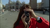 CU SLO MO Woman shooting film at camera with old super 8mm film camera on Place San Marco/ Venice, Italy