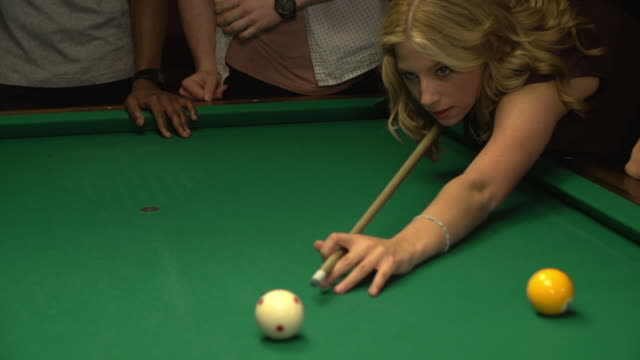 woman shooting pool with friends at a nightclub
