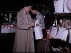 1965 MS woman shopping in department store/ ZI CU woman placing wallet and keys inside purse shoplifting the purse/ Berkeley, California