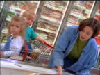 Woman shopping with two small children in supermarket choosing turkey in frozen food section