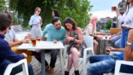 MS ZI ZO Woman showing smartphone to man during party with friends on rooftop deck
