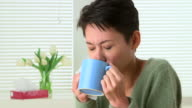 Woman sick with cold sneezing and drinking tea