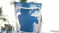 Woman silhouetted in sun lounger using mobile ohone