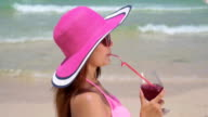 Woman sipping a refreshing cocktail on the beach,Slow motion