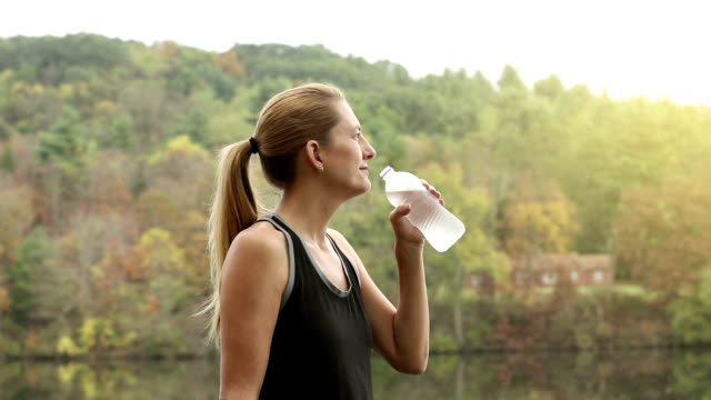 Woman Sipping Water Outdoors In Fall