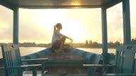Woman sits at front of boat at sunset