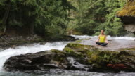 Woman sits by the river and does some yoga