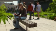 Woman sits on a bench on the Highline park, while reading a book on her IPad.