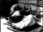 1936 WS Woman sits on ground weaving rug and is joined by another woman