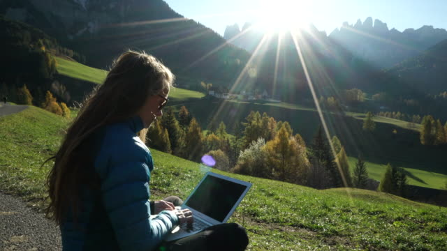 Woman sits on mountain trial using laptop