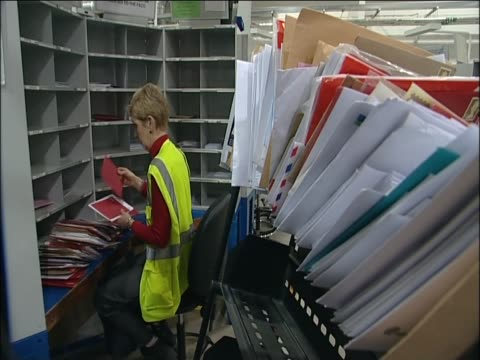 Woman sits sorting mail at the British forces Post Office headquarters at RAF Northolt