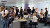 WS Woman sitting at desk during office party as coworkers stand around talking and drinking/ London, England