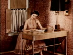 1956 MONTAGE Woman sitting at table leafing through magazine in room / USA
