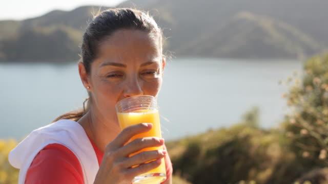 Woman sitting by lake drinking orange juice