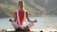 Woman sitting by lake practising yoga