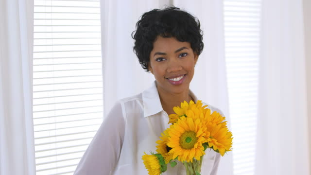 woman sitting by window holding sunflowers