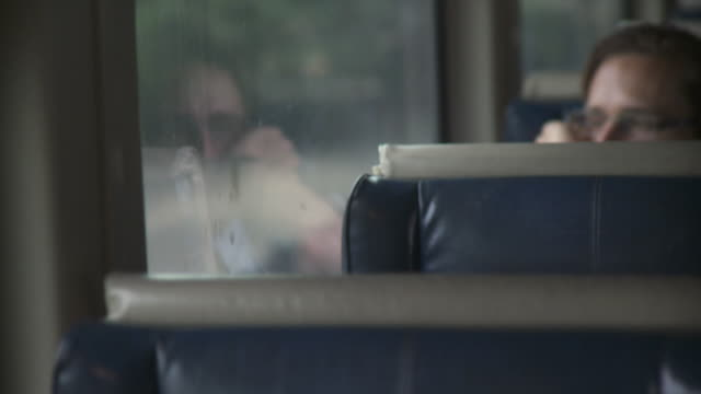 CU SELECTIVE FOCUS Woman sitting by window in moving train / New York City, New York, USA