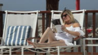 WS Woman sitting deck chair reading magazine and talks on mobile phone / Golf De Son Termes, Bunyola, Mallorca, Baleares, Spain