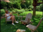 Woman sitting in Adirondack chair reading book in backyard near 2 dogs