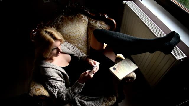 Vrouw zitten in de leunstoel en het gebruik van de telefoon