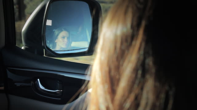 MS POV Woman sitting in car and watching herself in side mirror / Palmdale, CA, United States