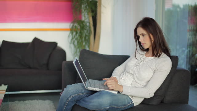 MS Woman sitting in living room using laptop / Kleinmachnow, Brandenburg, Germany