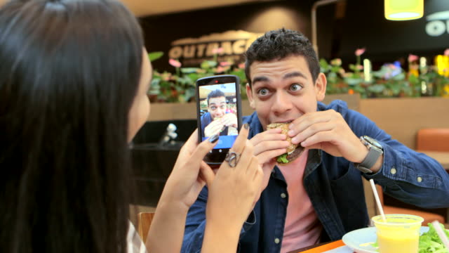 MEDIUM HANDHELD woman sitting in restaurant using smartphone to take photos of man eating and smiling indoors