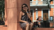 MS Woman sitting in street talking on cell phone, another woman arriving, Merida, Yucatan, Mexico
