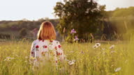 DS Woman sitting in the middle of a spring meadow