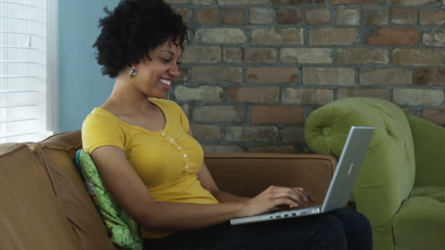 woman sitting on a couch typing on a laptop computer