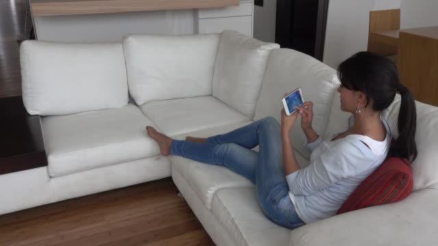 Woman sitting on a couch using a smart home app