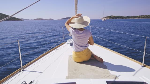 WS-Frau sitzt auf einem Deck eines Segelbootes Segeln