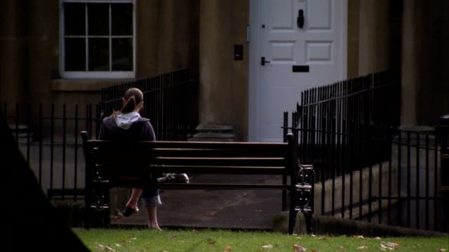 Woman sitting on a park bench near a Georgian terrace in Bath, England. Available in HD.