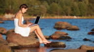 Woman Sitting on Beach and Using Laptop