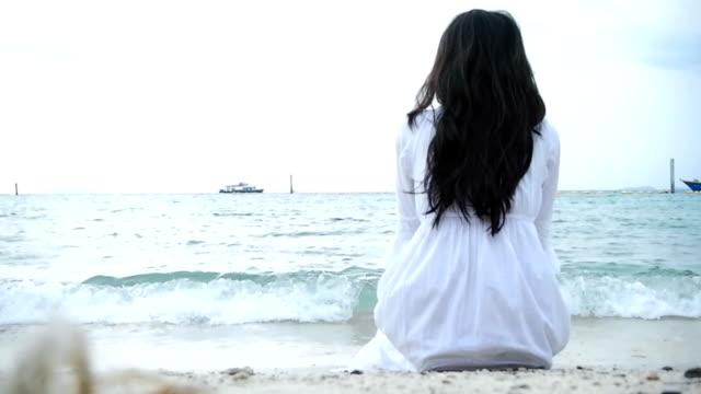 Vrouw zittend op het strand kijken naar de oceaan golven