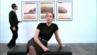 Woman sitting on bench at gallery opening and looking at artwork across room / man looking at three-panel print of a Weimaraner by William Wegman on wall behind woman / man bringing woman drink / man and woman walking away from bench