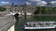 WS Woman sitting on bridge and ferry boat moving below bridge / Paris, Ile-de-France, France