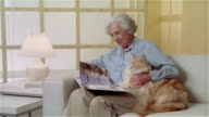 MS woman sitting on couch and looking at book while holding Maine Coon cat
